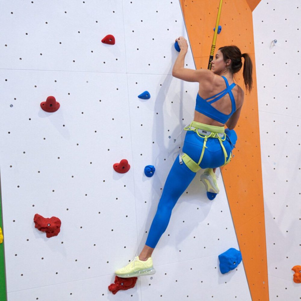 woman climbing indoor rock wall